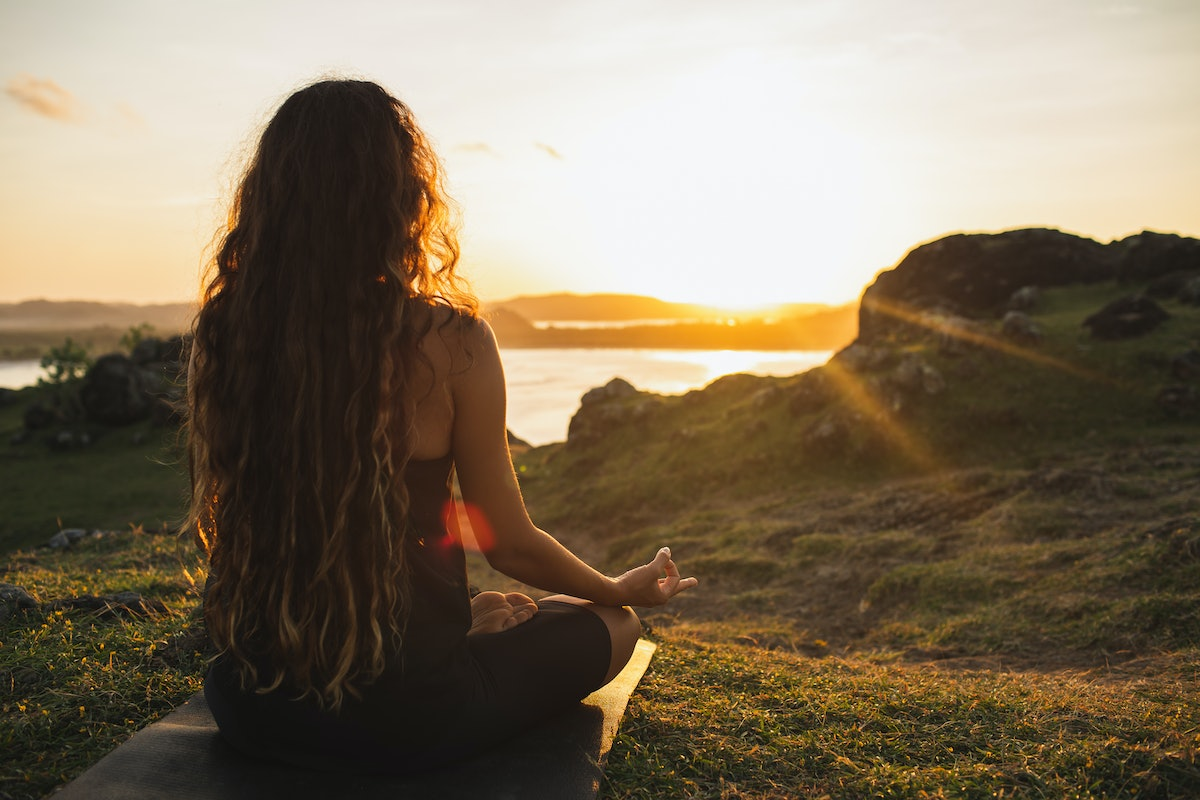 Woman meditating yoga alone at sunrise mountains. View from behind. Travel Lifestyle spiritual relax...