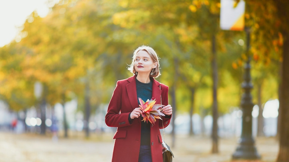 Beautiful young woman with bunch of colorful autumn leaves walking in park on a fall day