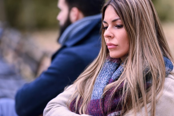 Couple sitting in park having relationship problems