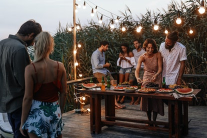 Group of young men and women enjoying summer holiday at outdoor party.