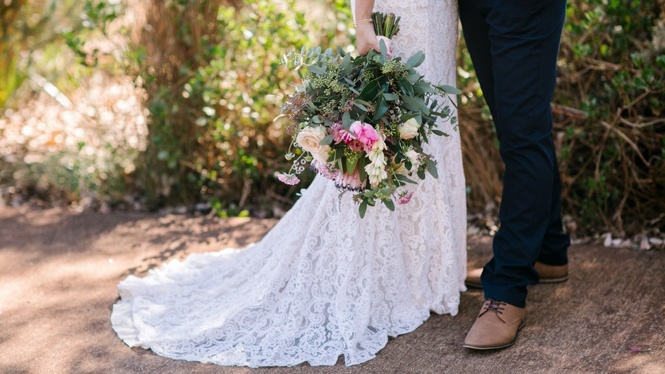 Bohemian bride and groom with big beautiful flower bouquet on wedding day