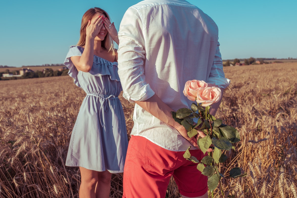 Beautiful and young couple man and woman, summer in a wheat field, behind gift is bouquet of flowers, surprise and tenderness, happy smiles. Romantic relationships, love love mutual understanding.