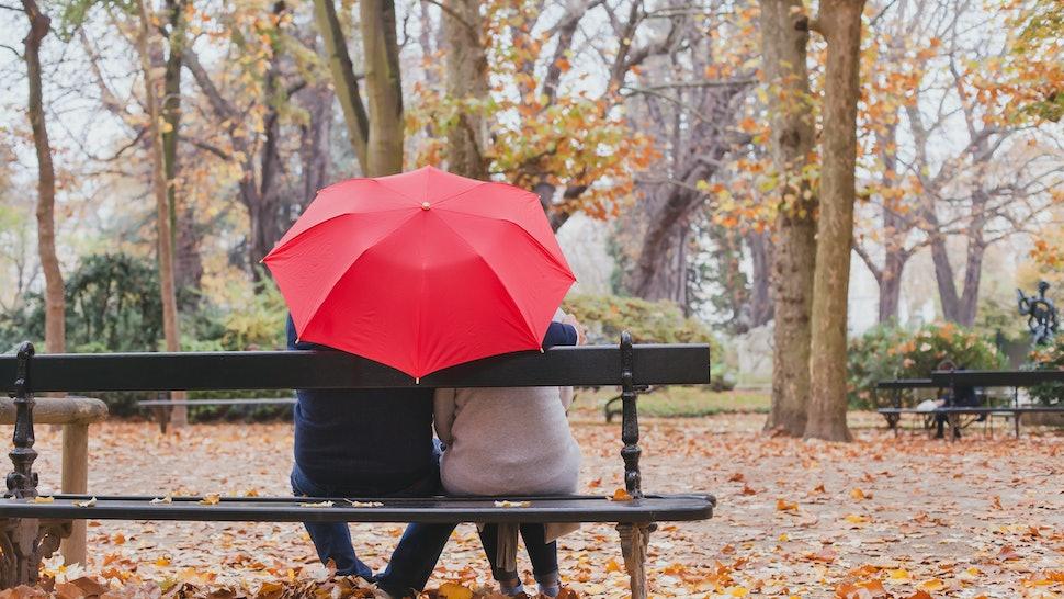 couple under umbrella in autumn park, love concept, happy elderly people