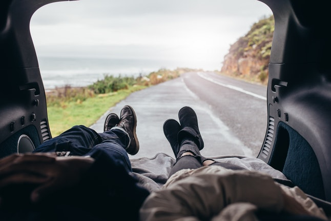 POV shot of couple lying in the car trunk. Man and woman relaxing in the car trunk along the road.
