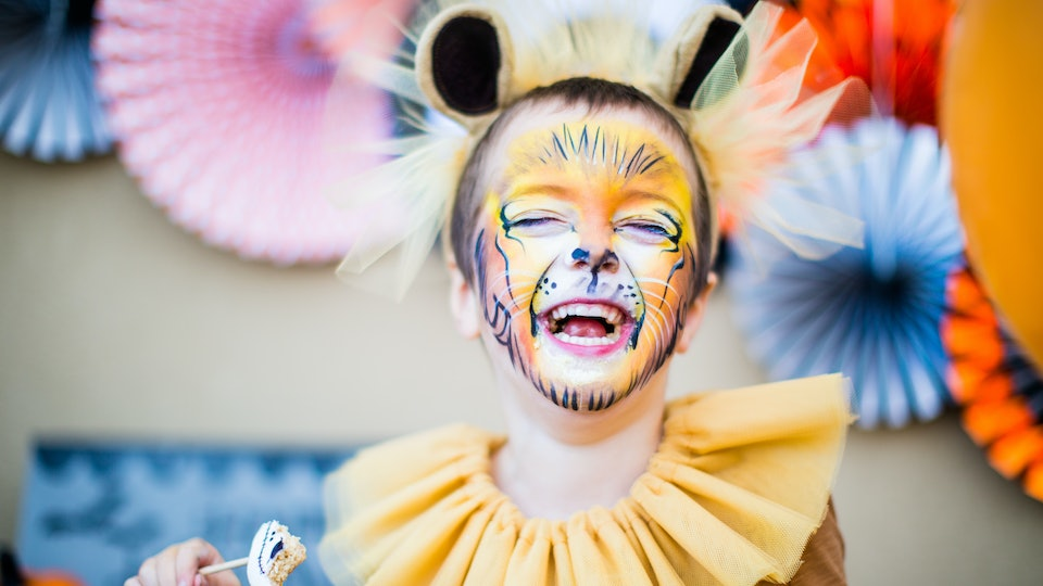 Boy in lion fancy dress laughing at children's halloween party