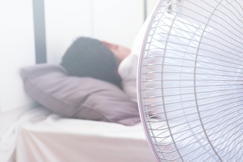 A man Sleeping on the bed and turn on the fan over the head risks of respiratory system.Health and m...