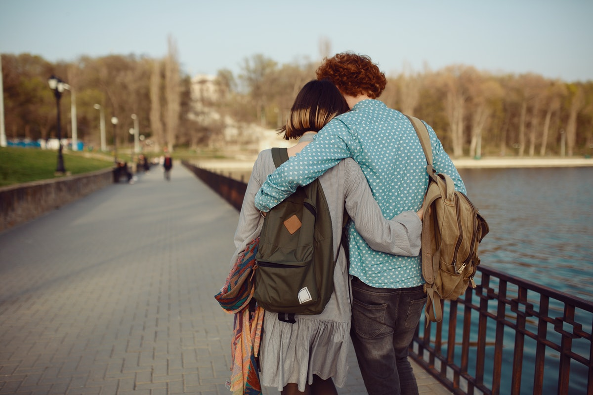 Happy hipster couple on holiday having fun and enjoy the time. Couple in love walking by the lake an...