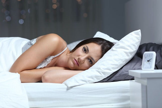 Angry insomniac woman looking at camera lying on a bed in the night at home