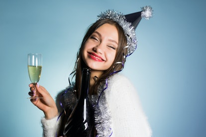 happy drunk woman in festive cap with a glass of champagne
