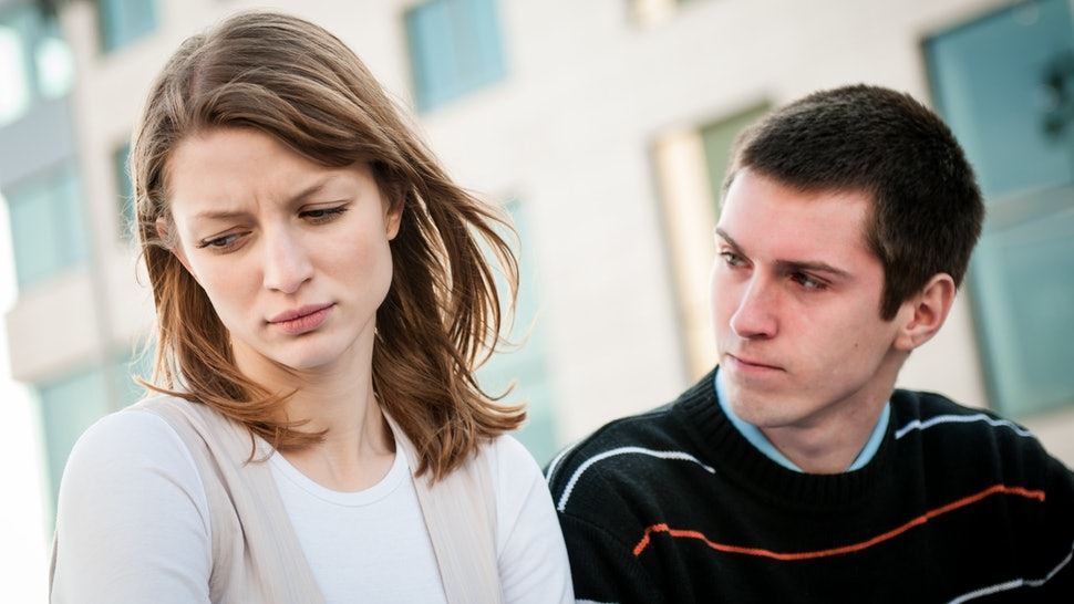 Lifestyle image of young woman and man outside on street having relationship problems