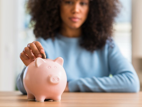 African american woman saves money in piggy bank with a confident expression on smart face thinking serious