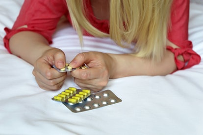Woman with pills, female hands on the bed with a blister pack of tablets. Blonde girl taking medicat...