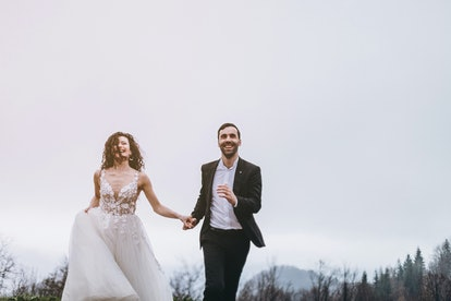 a man and a woman who run by holding hands against a white skies background. Happy and lovely couple of brides are running forward in misty weather in the mountains. Selective focus, noise effect