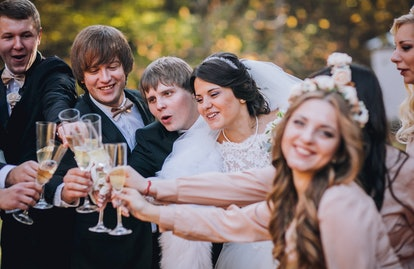 Wedding guests clinking glasses with the newlyweds at the park. Newlyweds with bridesmaids and groomsmen having fun. Toast. Champagne glass.