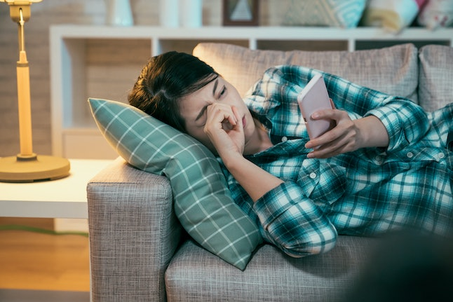 Sleepy tired asian woman rubbing eyes lying in sofa couch late evening time. Sad young beautiful girl reading message containing bad terrifying news on cellphone crying night at home frowning upset