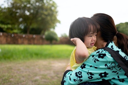 Asian children feel sad to hug mother in the garden.