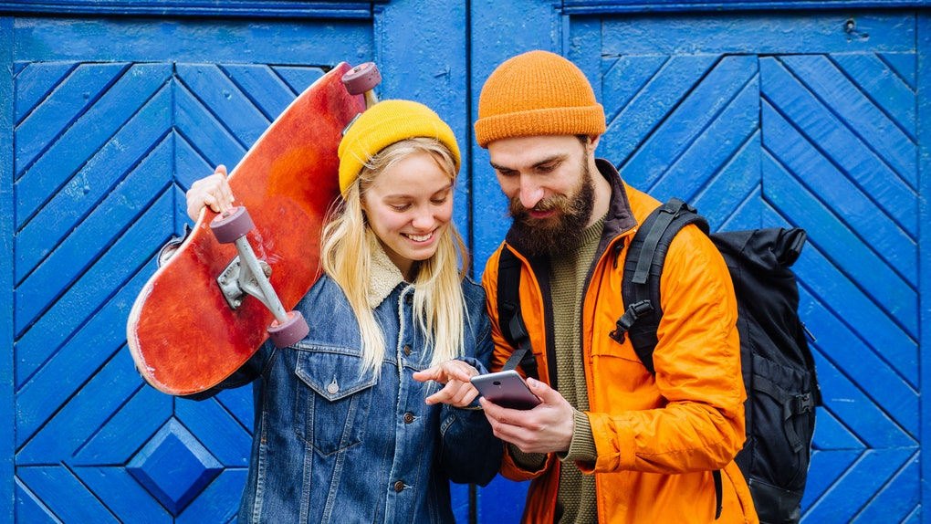 Happy american hipster friends longboarders showing something in smartphone on blue wooden background, trendy dressed couple laughing using smartphones apps outdoors in city street