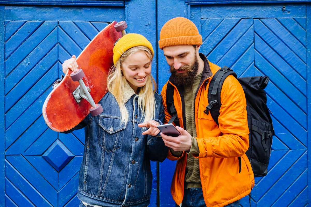 Happy american hipster friends longboarders showing something in smartphone on blue wooden backgroun...
