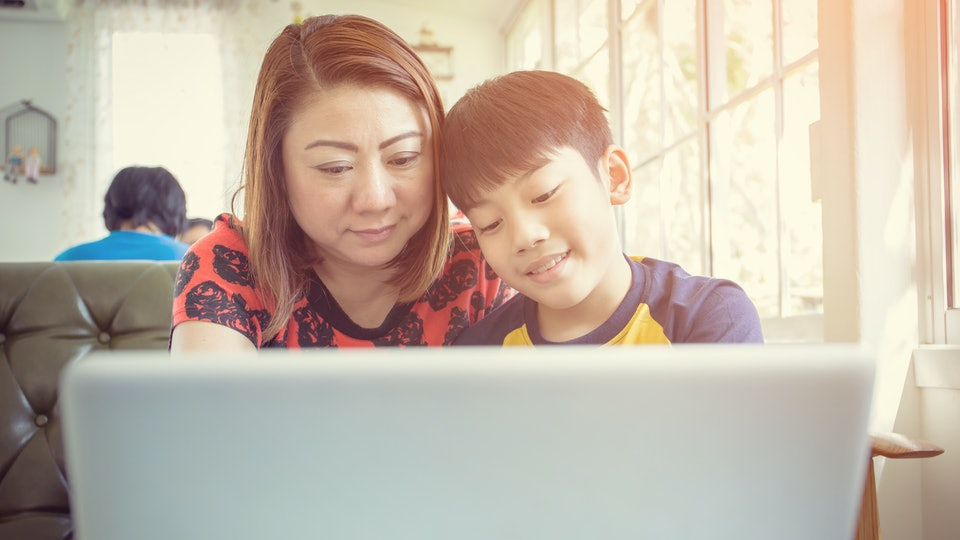Happy Asian Mother And Son Sitting At Desk Using Laptop At Home