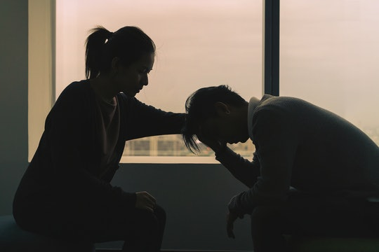 couple sitting near window in dark room at evening time with low light environment