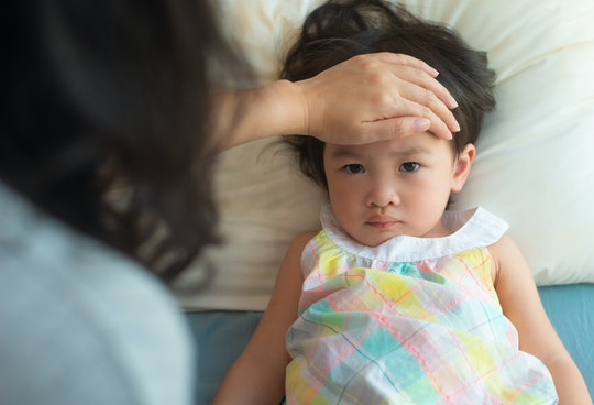 mom checking her daughter's forehead for fever