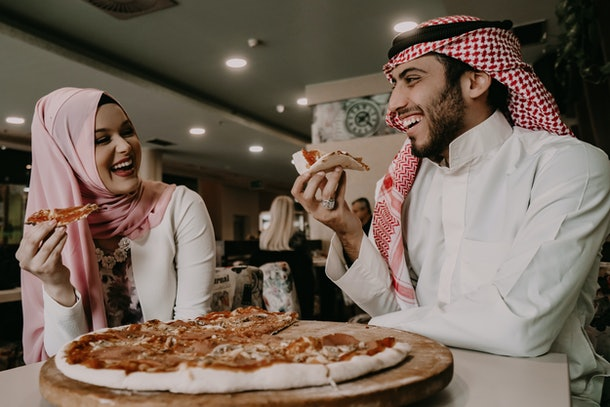A couple eats pizza in a restaurant as part of a surprise birthday party.