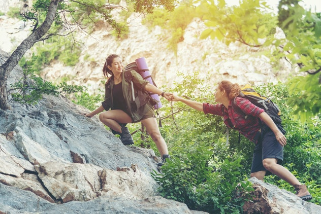 Summer Outdoors. Group Hiker woman helping her friend climb up the last section of sunset in mountains. Traveler women teamwork walking hea in outdoor lifestyle adventure hike camping. Travel Concept.
