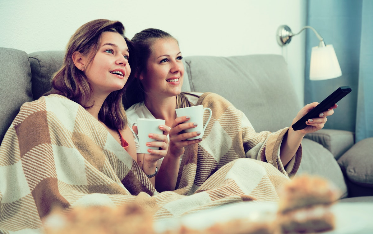 Girlfriends are watching TV and drfinking tea at home.
