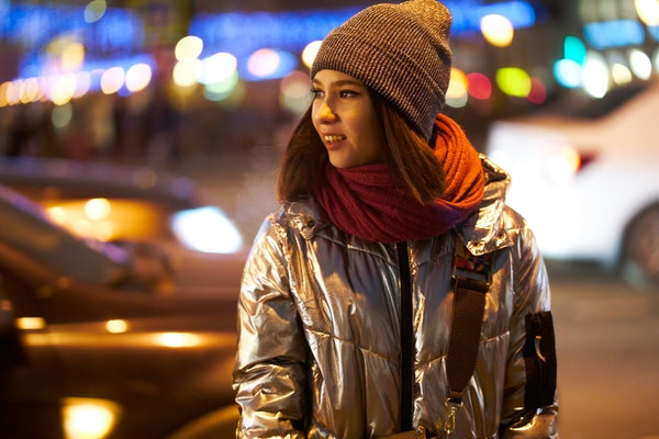 girl in a winter jacket a red scarf and hat. on the background of Christmas lights. bokeh Garlands. looking away