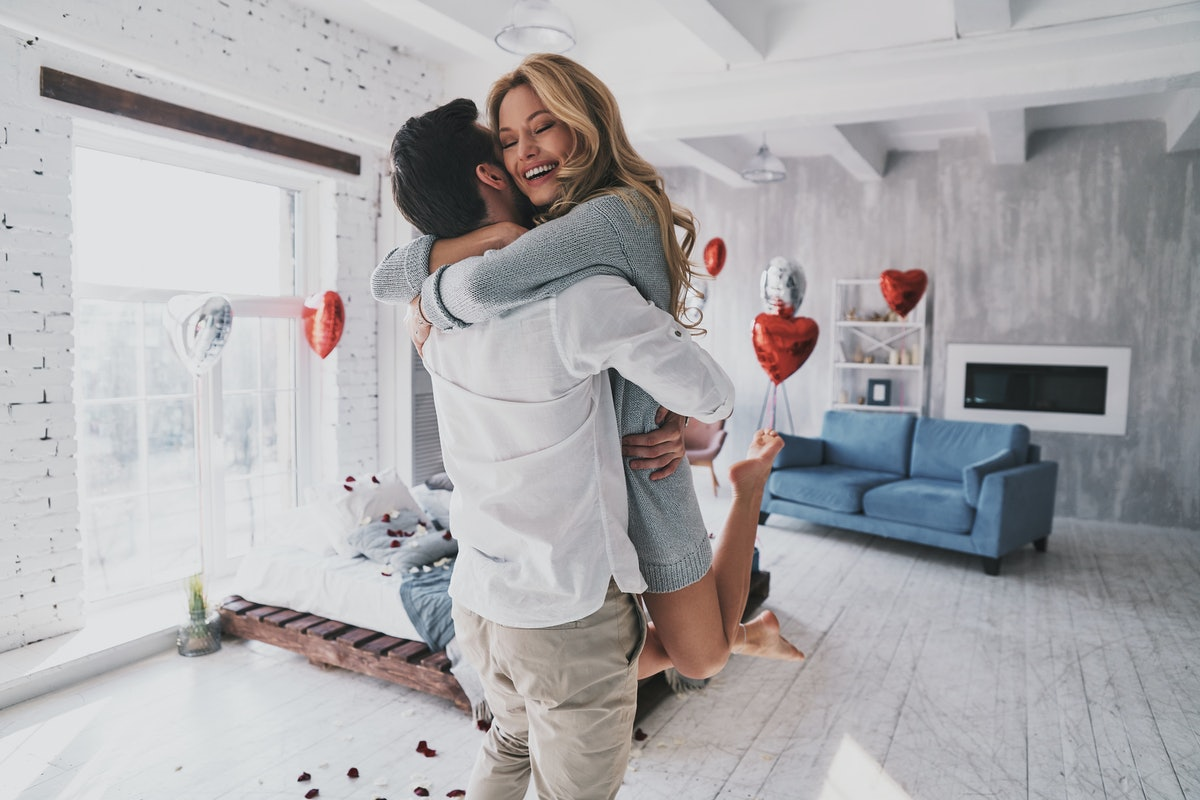 A couple hugs and laughs while celebrating a birthday in their bedroom that's filled with balloons and rose petals.