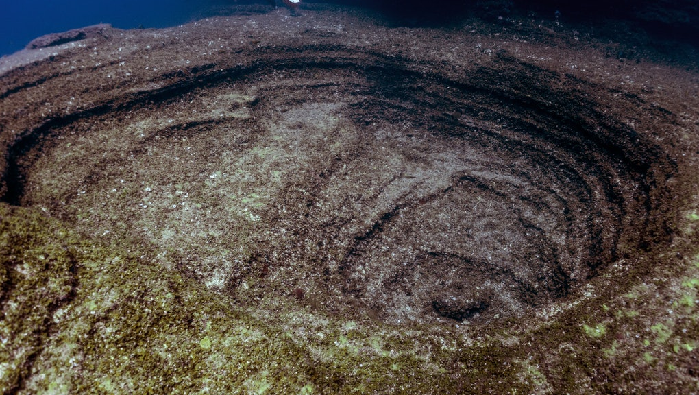 Diver floating on underwater volcano crater