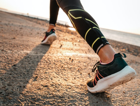 Sports and running. A woman runs along the sea. Close-up of feet in sneakers