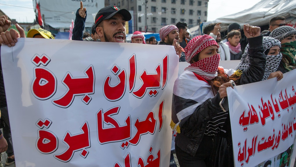"Anti government Iraqi protesters chant anti Iran and anti U.S. slogans and carry a poster that reads in Arabic ""Iran get out, U.S. get out and Baghdad is free"" during the ongoing protests in Tahrir square, Baghdad, Iraq"