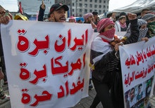 Anti government Iraqi protesters chant anti Iran and anti U.S. slogans and carry a poster that reads...