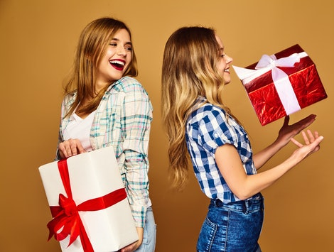 Christmas, x-mas, concept.Two smiling beautiful women in stylish clothes.Girls posing on golden background.Models with big gift boxes.Having fun,ready for celebration.Bright holiday of best friends