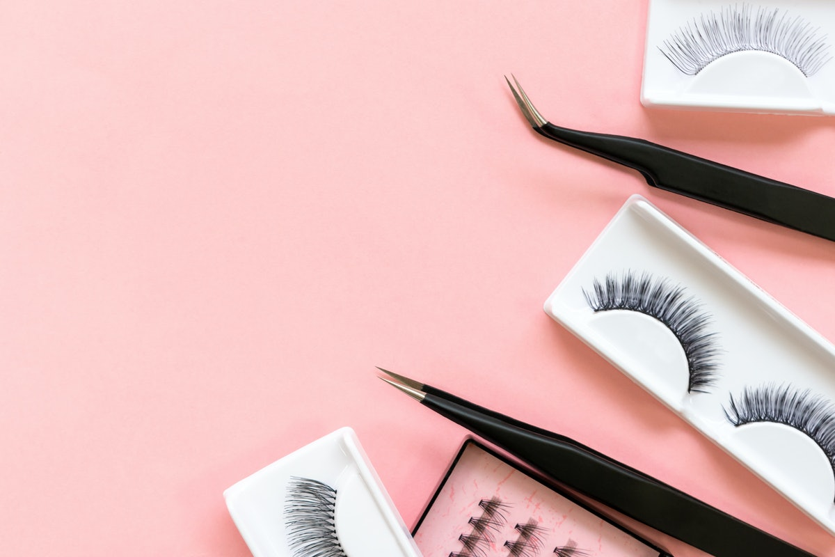 Tools for eyelash extension on trendy pastel pink background. False eyelashes and tweezers. Beauty shop. Makeup cosmetics. Top view, flat lay. Place for text. Layout