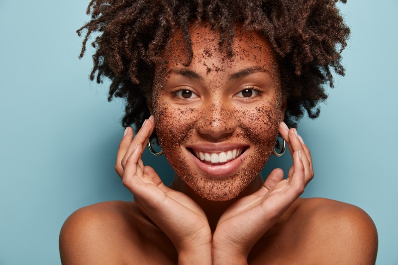 Photo of smiling black woman has cleansing mask or scrub on face, smiles broadly, enjoys beauty treatments in salon, touches soft skin, looks happily at camera, isolated over blue background