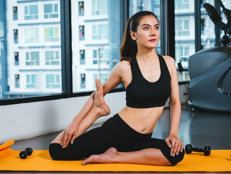 Beautiful woman yoga stretching body before exercise workout out at fitness GYM