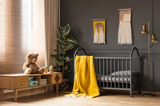 a rustic nursery with gray crib and yellow blanket