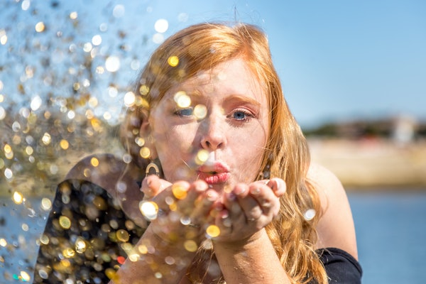 A woman with red hair blows glitter out of her hands on a sunny day at the beach.