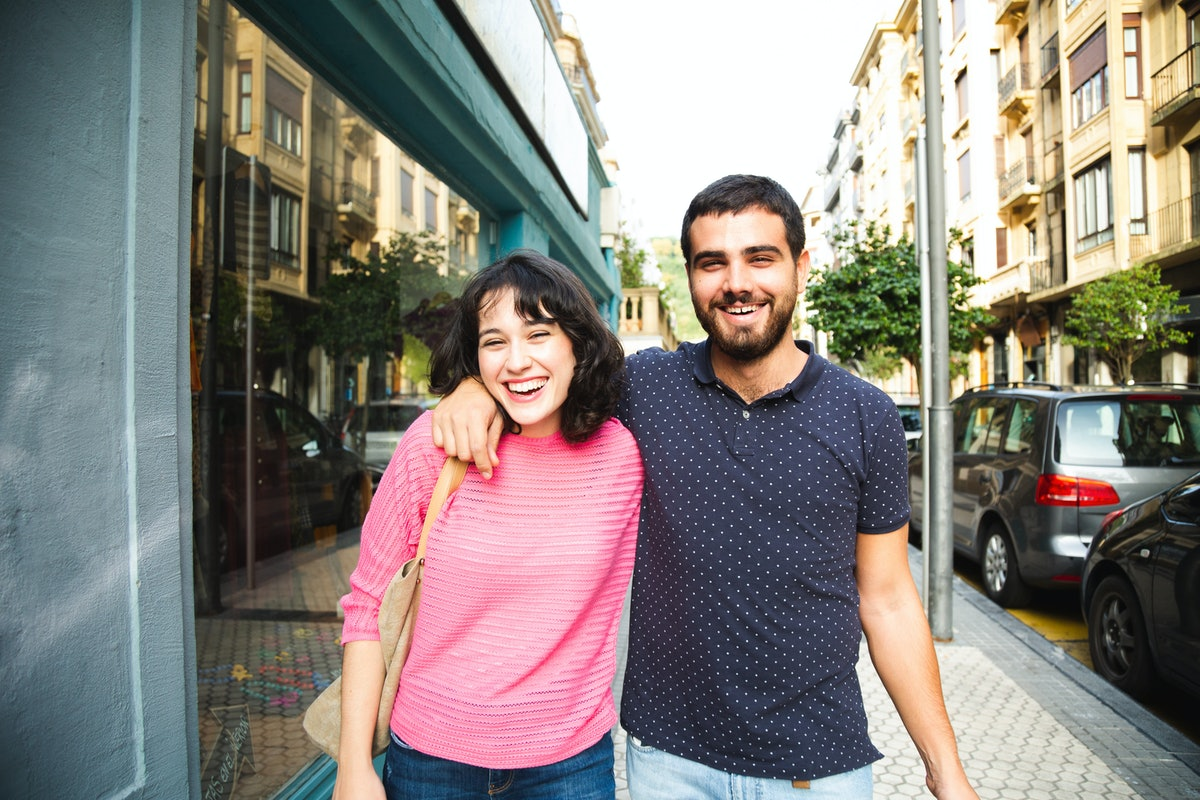 A happy couple walks down a city street on a sunny day and laughs.