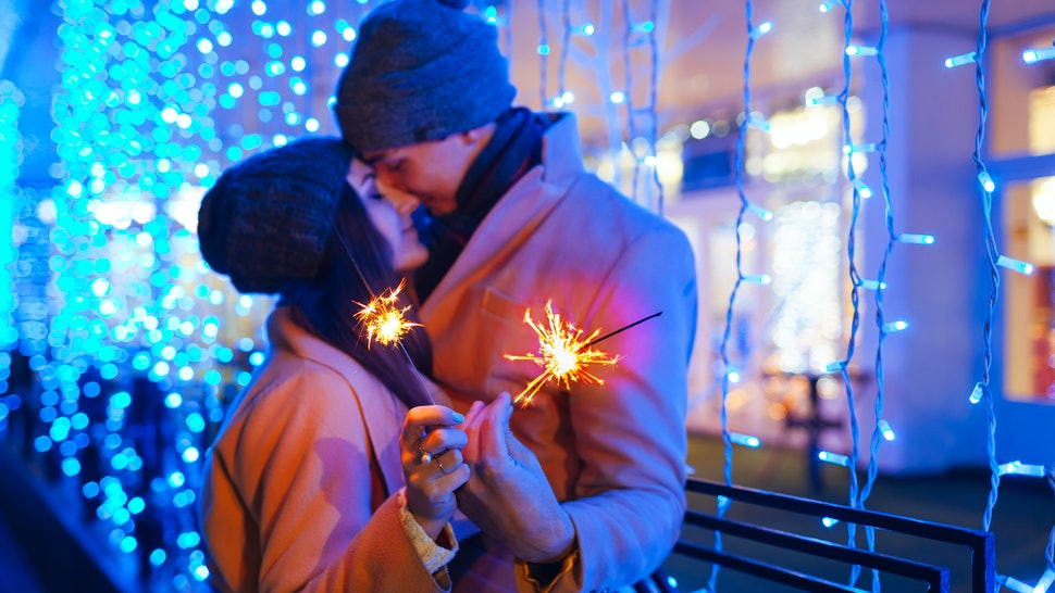 Christmas and New year fun concept. Couple in love burning sparklers by holiday illumination outdoors. Festive holidays