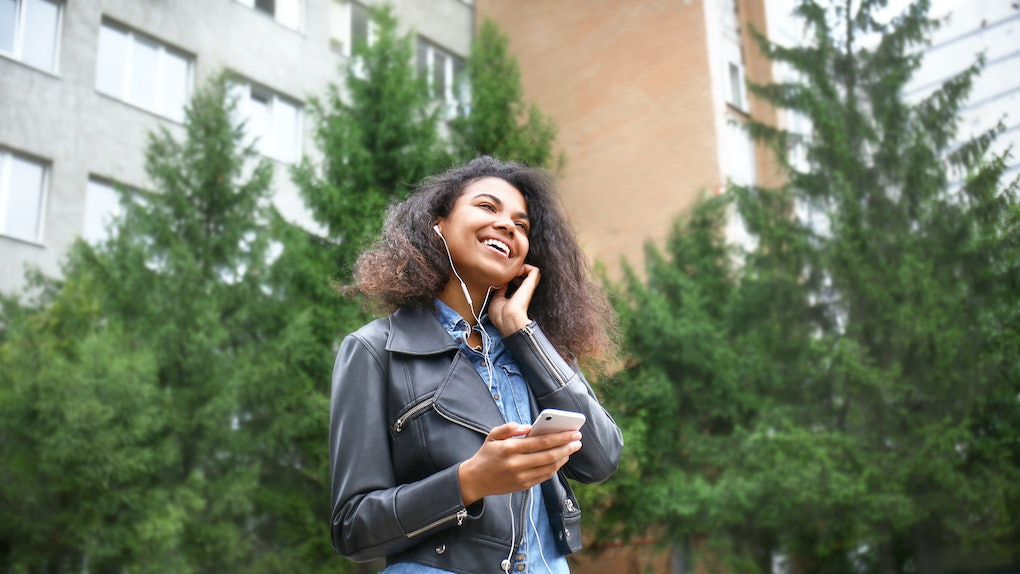 Beautiful young African-American woman listening to music outdoors