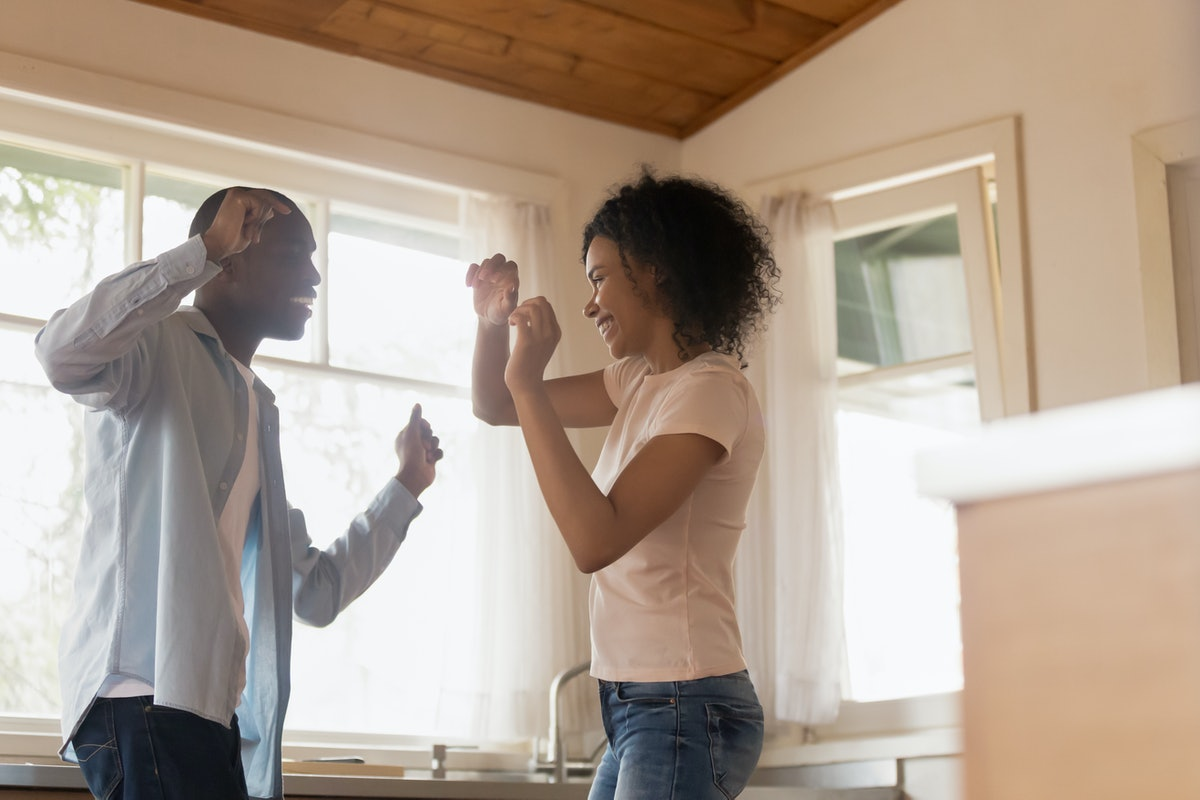 Excited african American millennial husband and wife have fun celebrating anniversary at home, smili...
