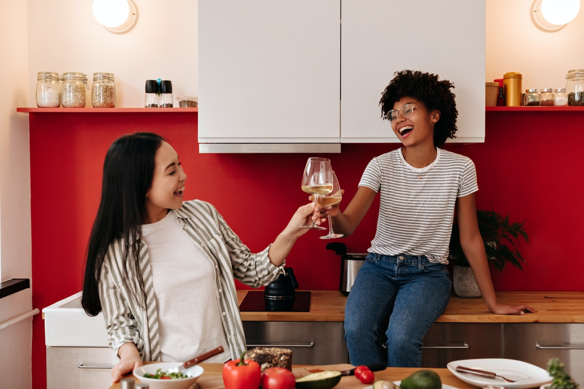 Funny friends laugh and clink glasses with champagne in kitchen