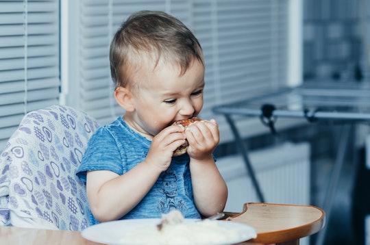 little boy eating chicken in high chair