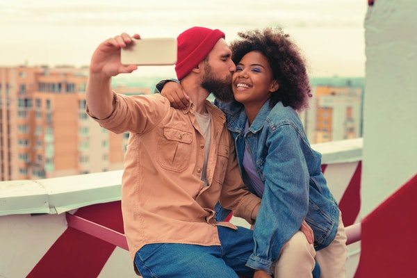 Kiss and selfie. Loving young man kissing his smiling happy girlfriend while sitting on the roof with her and taking selfies