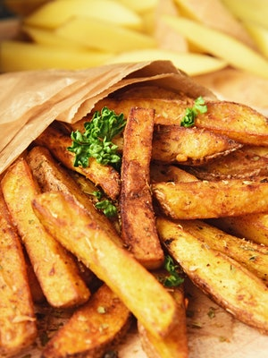Homemade Crispy Seasoned French Fries.French fries  with spicy seasoning in brown paper bag on wooden broad.