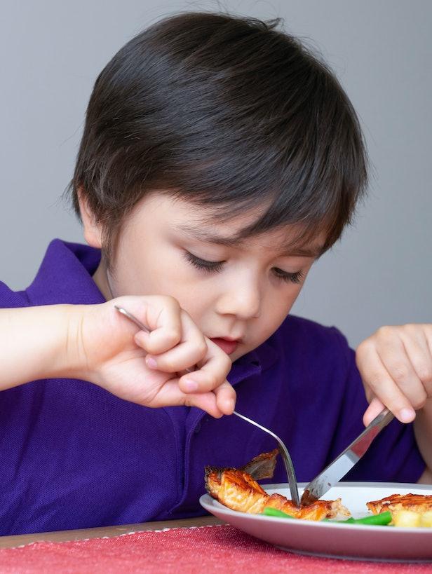 little boy eating salmon