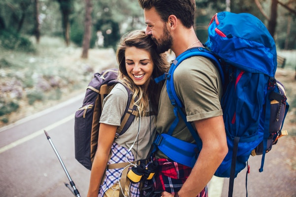 Romantic couple hiking on the path in mountains